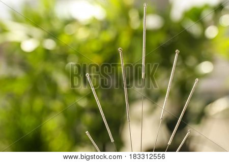 Needles for acupuncture on blurred background