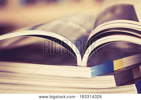 Close up opened magazine page with blurry bookshelf background for publication concept extremely DOF with vintage retro color tone