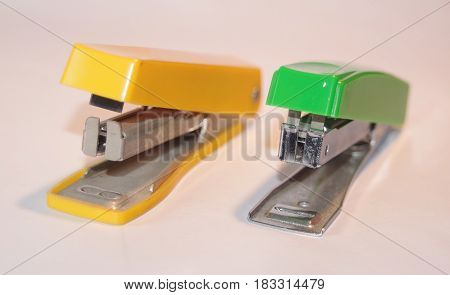 Two paper staplers, yellow and green side by side.