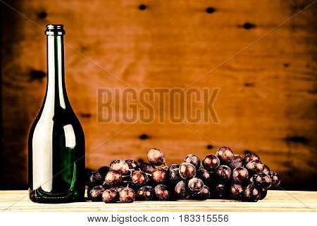 wine bottle with grapes on a wooden background