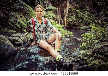 Beautiful female hiker sitting by stream