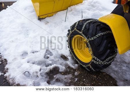 Yellow snowplow truck cleared the snow-covered road after snowfall during a cold snowstorm. Wheel of snowmobile with chain. Outdoor in winter day.