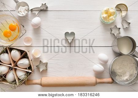 Baking cookies background. Cooking ingredients for dough and pastry, eggs yolks, flour and cookie cutter on white rustic wood. Top view with copy space, mockup for menu, recipe or culinary classes.