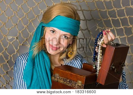 Beautiful woman holding a pirate with a chest on the background of a fishing net