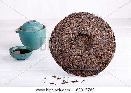 Round flat disc of puer tea on white. Pressed Chinese fermented Pu-erh tea.