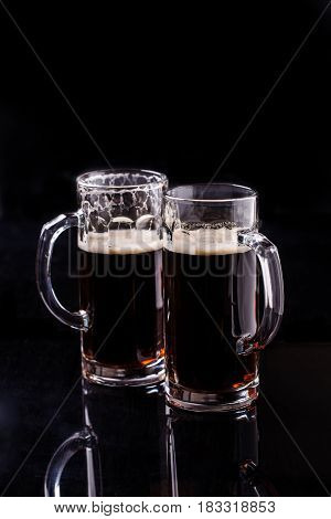 Two mugs of dark beer on black background