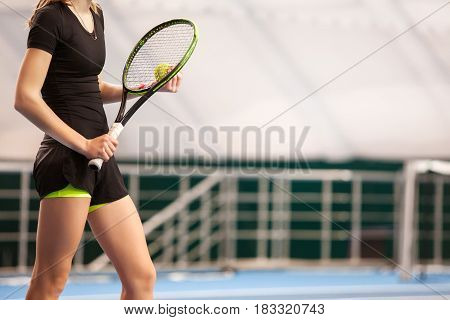 The legs of young girl in a closed tennis court with ball and racket