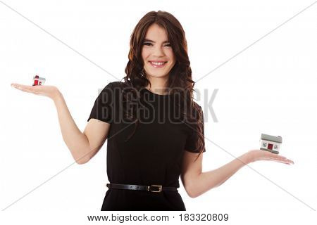 Buying new home concept - woman holding mini house.