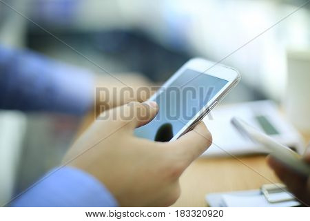 Close up of a man using mobile smart phone in modern office