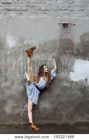 ballerina in a short dress and boots near a concrete wall near a basketball ring