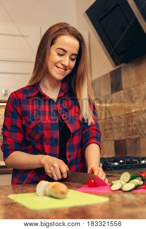 Vegetable cutting, woman cut tomato with a knife on chopping board. Female preparing healthy salad and smiling.
