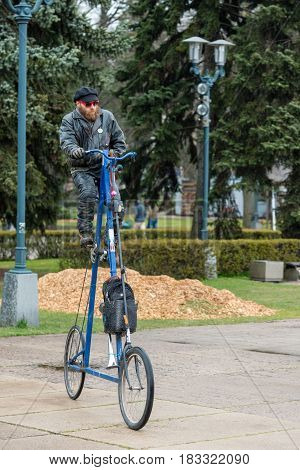 RIGA LATVIA - APRIL 22 2017: Tweed ride 2017. Unknown man rides a strange very high bike.