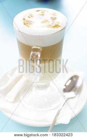 Latte macchiato cup on a blue table. Soft selective focus picture.