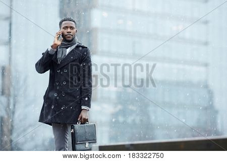 Man with briefcase looking at camera while calling outdoors