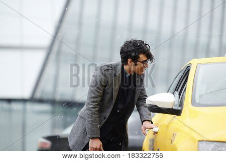 Businessman catching taxi on rainy day