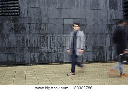 Hurrying men walking down trottoire along black wall of modern building