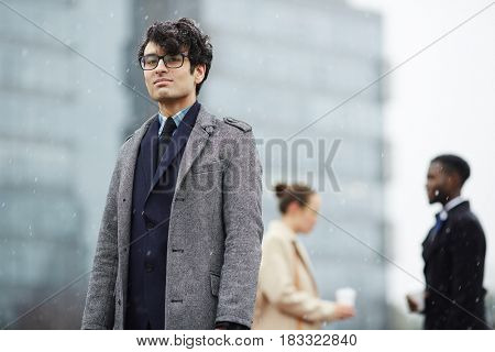 Businessman in coat on background of talking colleagues
