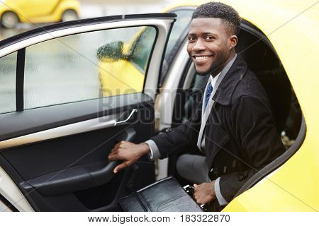 Successful lawyer getting out of taxi cab