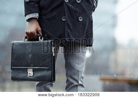 Low section of businessman with leather briefcase