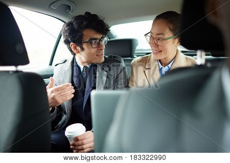 Modern traders having talk on backseat of car