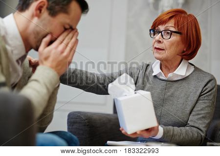 Experienced psychologist comforting patient and giving him box with paper tissues