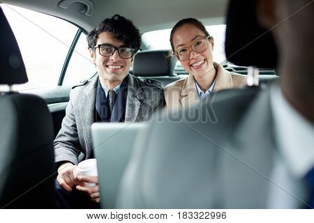 Two young managers looking at camera from backseat of car
