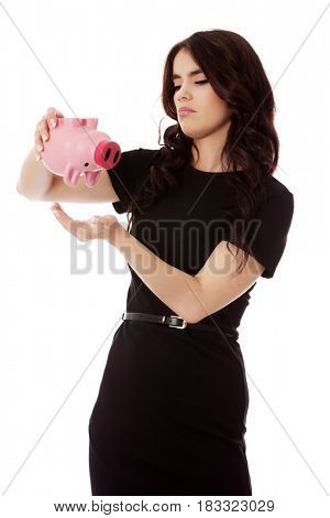 Happy businesswoman saving money in piggybank
