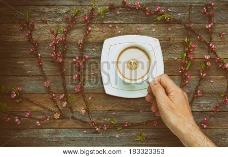 Cup with coffee milk in a male hand on a background of an old wooden table with peach branches with pink flowers top view. Retro toning photo with vignette