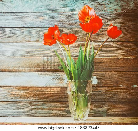 bouquet of flowers red tulips in a glass vase on a wooden background barn boards closeup. retro tinted photo