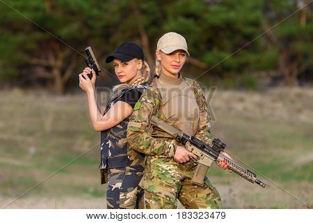 Two beautiful women rangers with weapon in camouflage on the forest background
