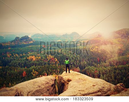 Man With Camera. Photographer Takes Photos With Mirror Camera And Tripod On Peak