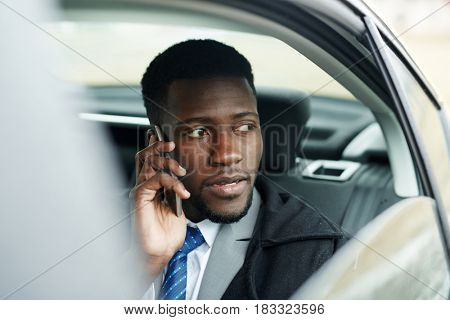 African-american businessman driving car and talking on cellphone