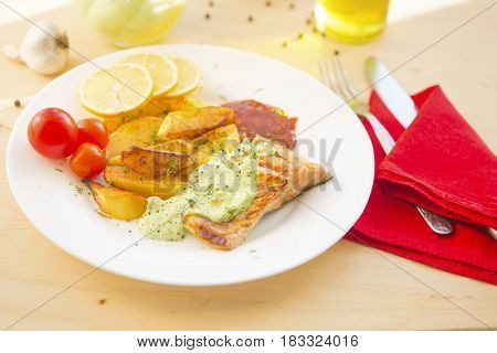 Fried Salmon And Vegetables On Plate On Wooden Table
