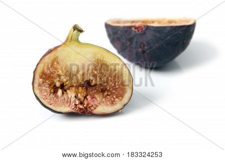 Fresh black genoa fig cut through to show the flesh and seeds inside on white background ,edible fruit, food.