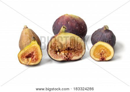 Several varieties of ripe common figs cut through to show the flesh and seeds on white background..