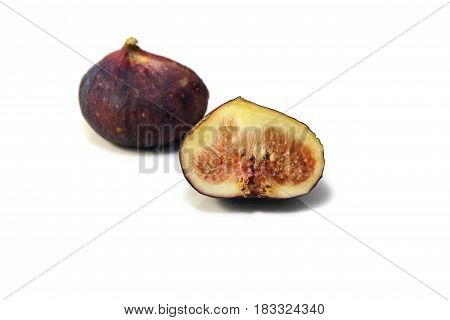 Black genoa figs cut through to show the flesh and seeds on white background.