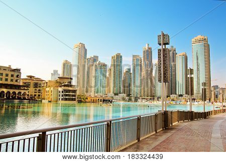 Downtown Dubai skyline view from the Dubai fountain. Modern city cityscape with skyscrapers sidewalk with perspective in sunny day.