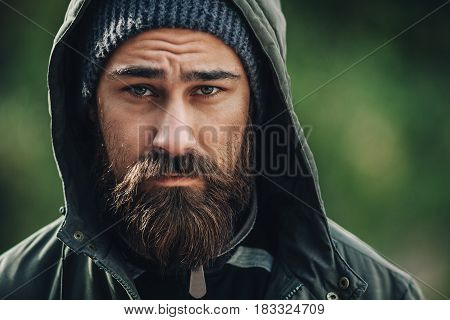 Outdor porttrait of a handsome brutal bearded man with dark beard and mustache dressed in winter clothes covered with frost. Man wear coat hat and hood. look like hipster or tourist. Close up.