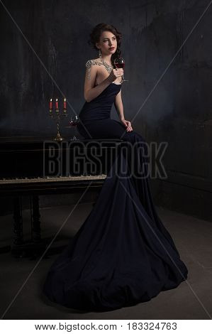 beautiful young woman in black dress next to a piano with candelabra candles and wine dark dramatic atmosphere of the castle. Bohemia.
