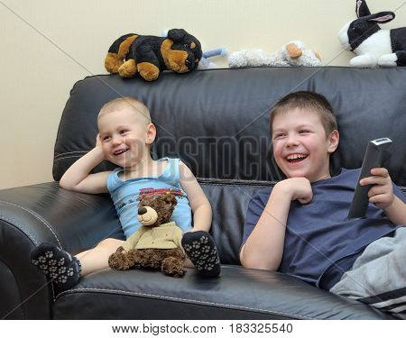 Happy brothers watching TV on leather couch and having fun together.