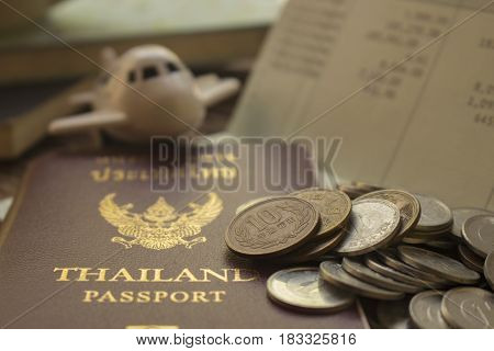 thailand passport with airplane toy and coins of japan concept idea saving for travel in japan.
