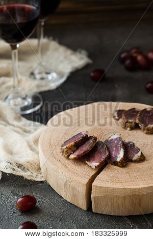 Slices Of Dried Meat On Wooden Cut, Red Grapes And Two Glasses Of Red Wine On Dark Rustic Background