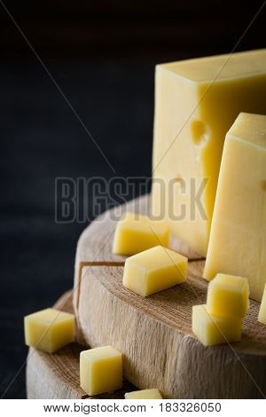 Closeup Of Swedish Hard Yellow Cheese With Holes Chopped On Wooden Slices On Dark Rustic Background