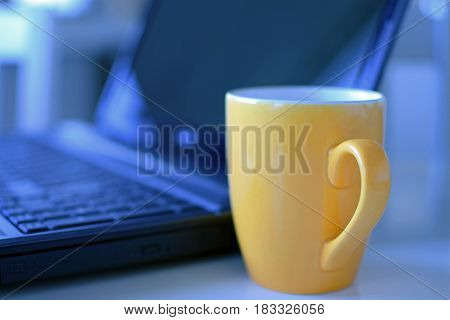 Yellow coffee mug and laptop on background.