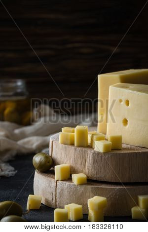 Swedish Hard Yellow Cheese With Holes Chopped On Wooden Slices With Green Olives On Dark Rustic Back
