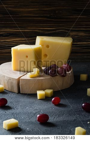 Swedish Hard Yellow Cheese With Holes Chopped With Red Grapes On Wooden Slices On Dark Rustic Backgr