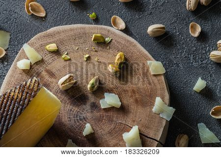 Chopped Spanish Hard Cheese Manchego On Wooden Cut With Pistachios On Dark Rustic Background, Top Vi