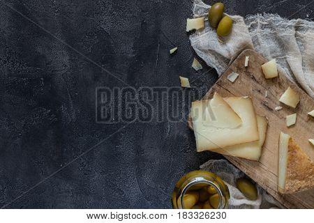 Italian Hard Cheese Pecorino Toscano Sliced And Chopped On Wooden Board With Green Olives On Dark Ru