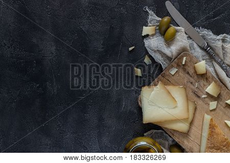 Italian Hard Cheese Pecorino Toscano Sliced And Chopped On Wooden Board With Knife And Green Olives