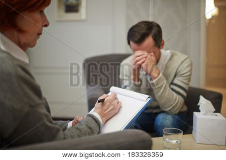 Psychiatrist writing down story of her patient